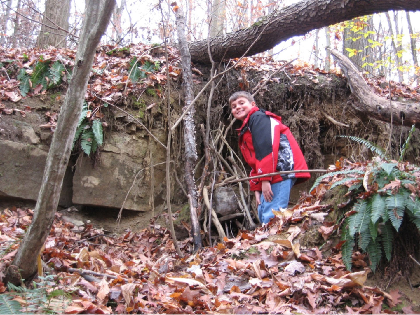 Boy at the elf house he has helped to build at Slate Run's natural play area.