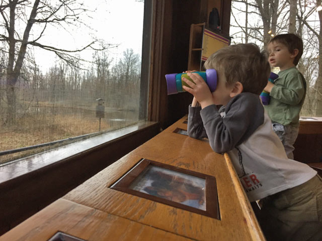 Kids use binoculars through nature center windows at Blacklick Woods