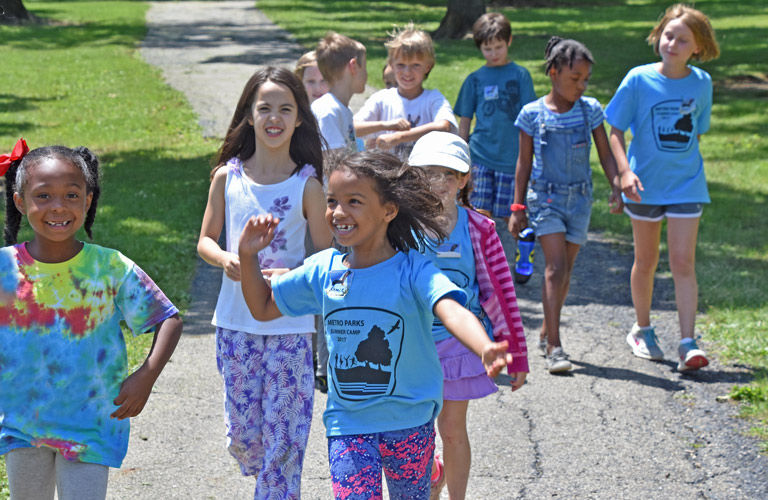 Kids laugh and sing on a path at a Sharon Woods Summer Camp.