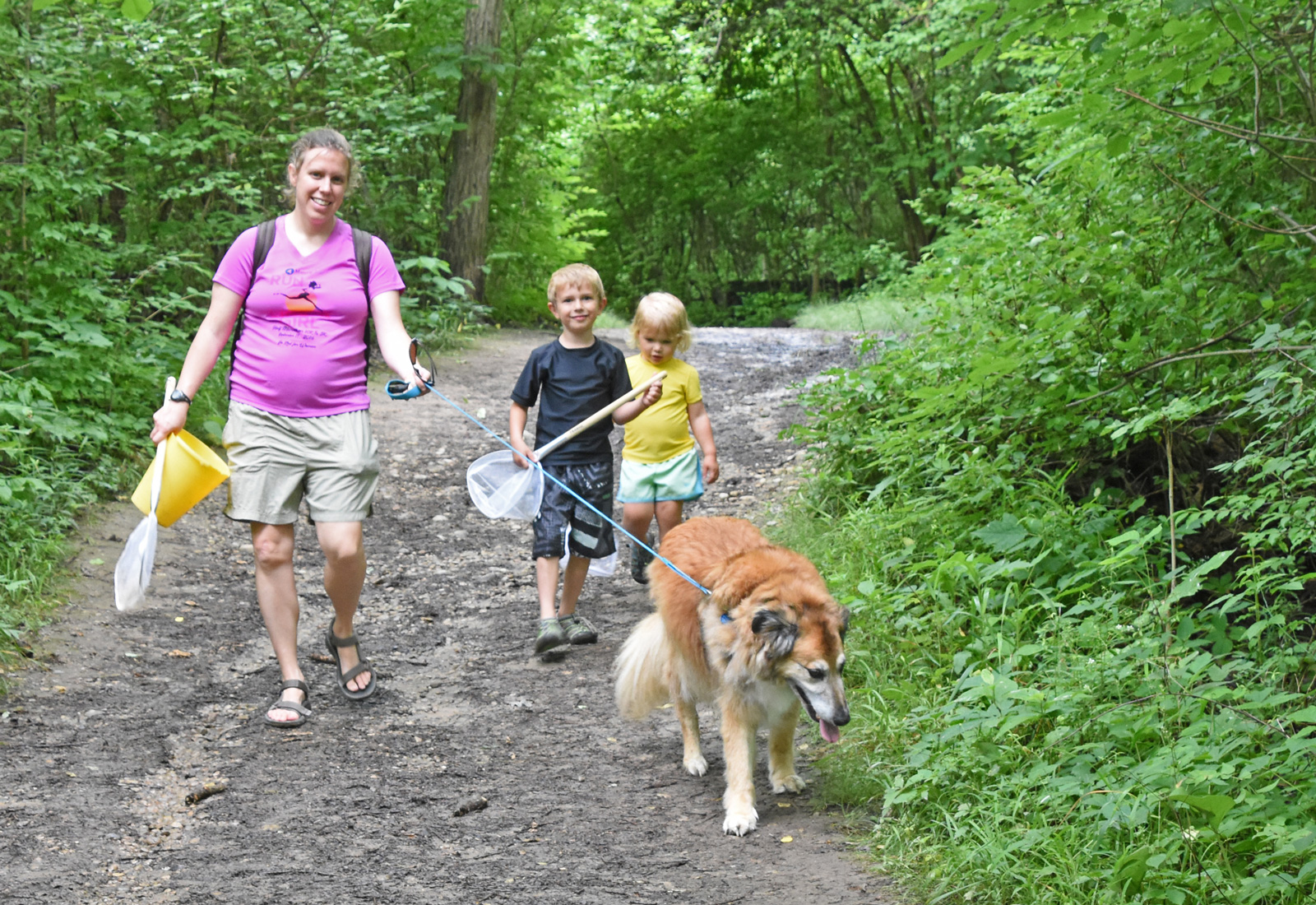 Mom, two kids and best furry friend on the Coyote Run Trail at Highbanks, heading to a creeking spot.