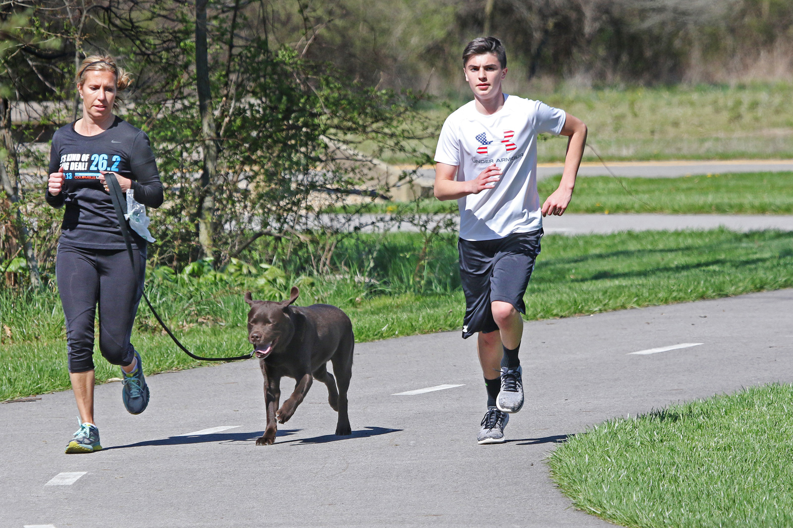 Park visitor and son run on the Beech Woodland Trail at Rocky Fork with their labrador.