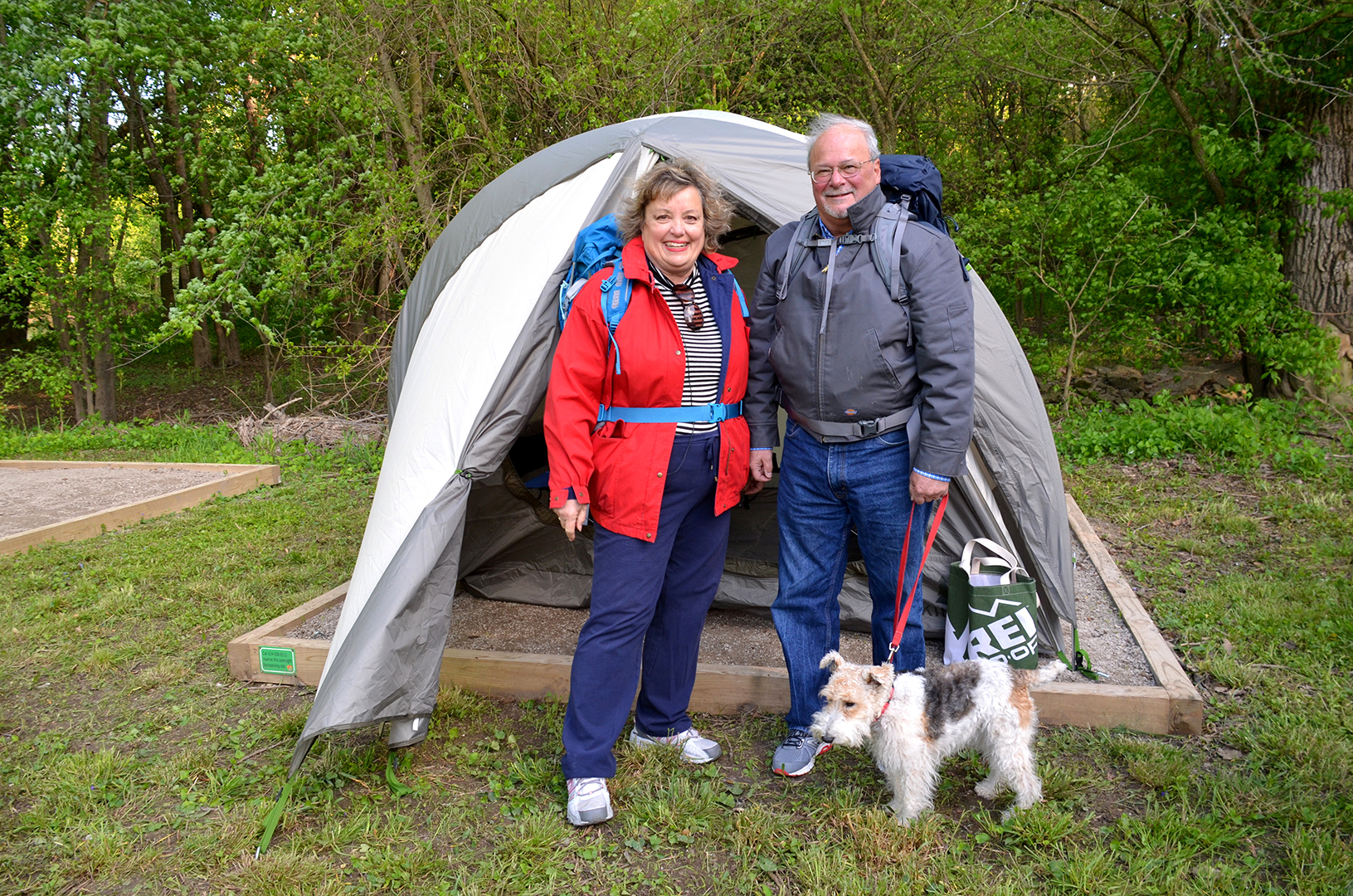Couple and dog outside their backpacking tent