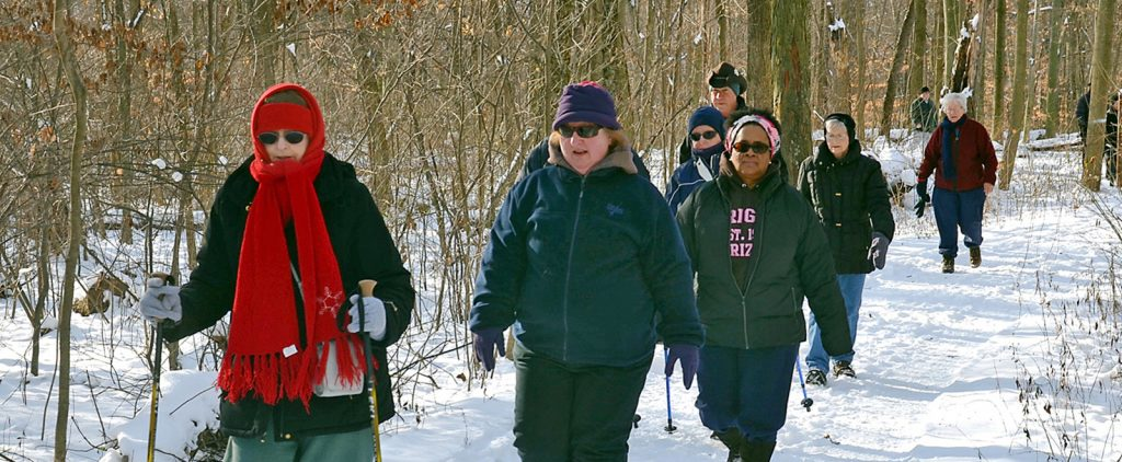 A group of Winter Hikers walk in the snow at Blacklick Woods