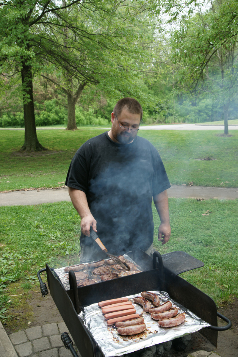 Visitor cooking burgers, sausage and hot dogs on a grill at the Indian Ridge Picnic Area at Battelle Darby Creek Metro Park