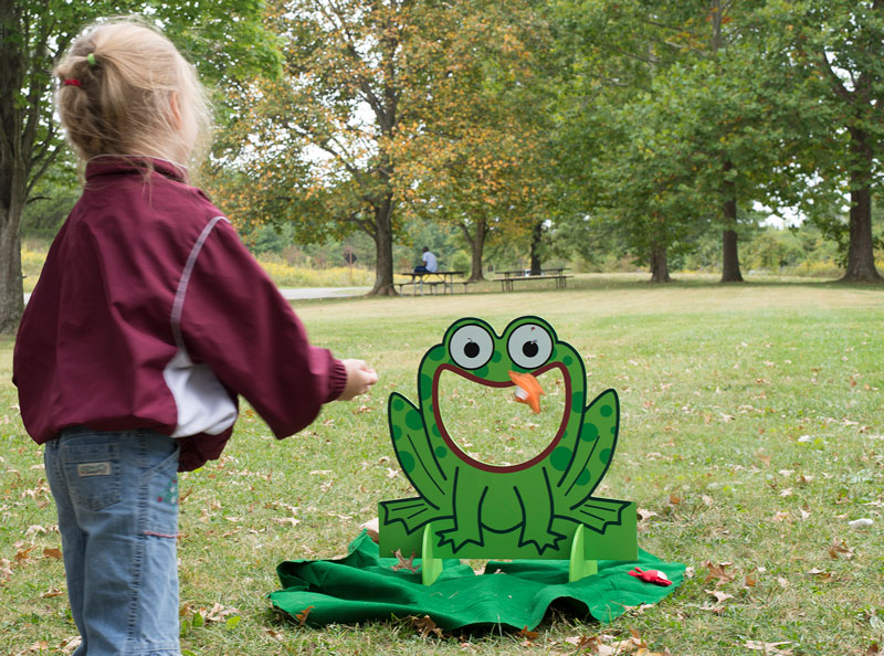 Girl at Blacklick Woods Creek Celebration tries to throw a cushion through the laughing frog's mouth.