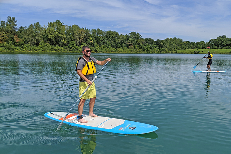 People paddleboard at Darby Bend Lakes at Prairie Oaks Metro Park
