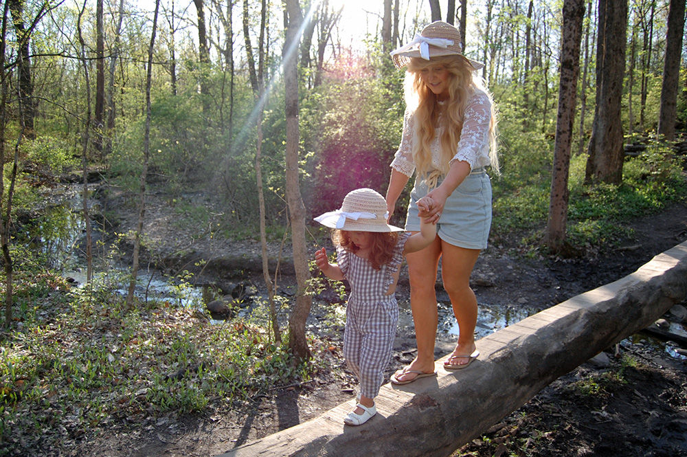 A woman and child walk across a log in the natural play area at Blendon Woods Metro Park.