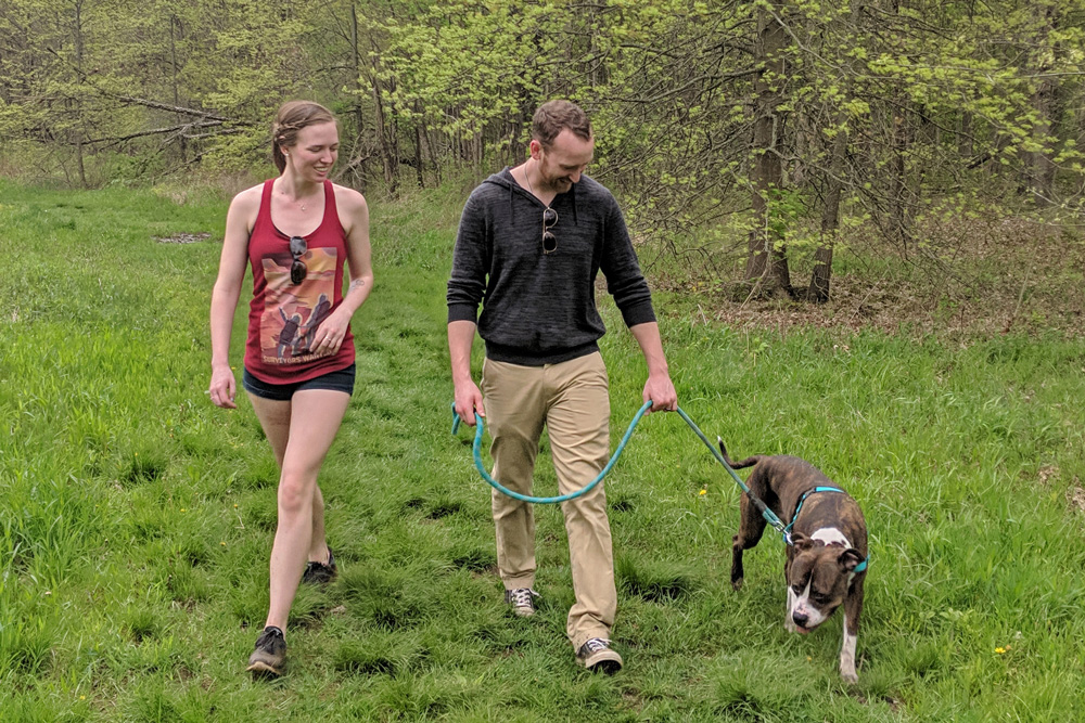 People walk a dog on the Goldenrod Trail at Blendon Woods Metro Park.